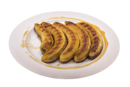 platanos fritos: plátanos fritos con miel en una placa en el fondo aislado Foto de archivo