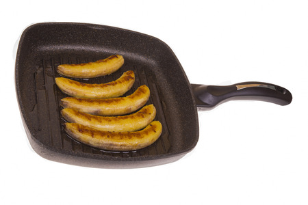 platanos fritos: fried bananas on a frying pan on the isolated background