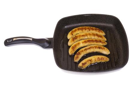platanos fritos: plátanos fritos en una sartén en el fondo aislado Foto de archivo