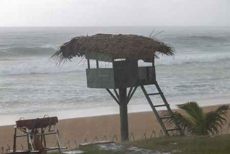 restless: saving tower during a heavy rain and the restless ocean Stock Photo