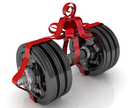 Dumbbell as a gift. Dumbbell tied with a red ribbon on a white surface