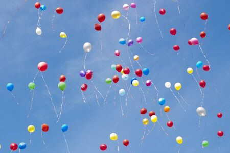 Multi-colored helium balloons fly in the sky 免版税图像