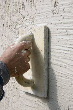 Fragment of the wall of the house with applied decorative plaster and the hand of plasterers with tool Stock fotó