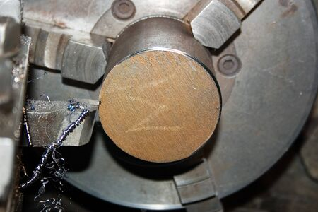 Cutting the end of a metal bar on a lathe. Close-up