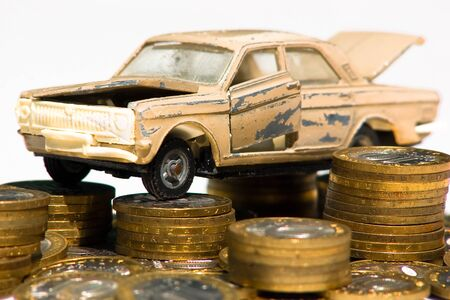 A model of an old car is standing on coins. The concept of expensive maintenance of an old car or its disposal Stock fotó