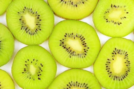 actinidia deliciosa: slices of fresh green kiwi fruits as a food background texture Stock Photo