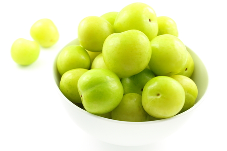 unripe: composition of fresh turkish can erik plum fruits in a small white bowl
