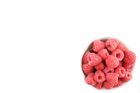 herbalism: fresh red raspberry fruits in a small white bowl