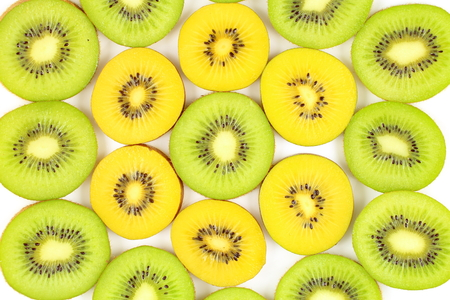 kiwi fruta: slices of fresh green and yellow kiwi fruits as a food background texture