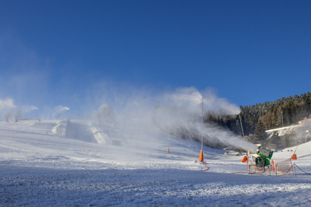 snowmaking with snow lances and snow cannons at ski resort Fichtelberg in Oberwiesenthal, Germany