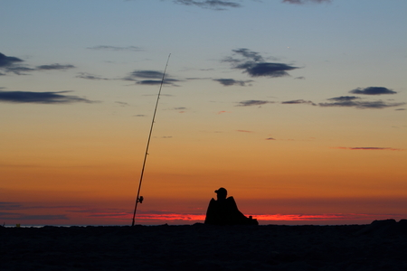 surf angler with fishing rod on the baltic sea beach at sunset