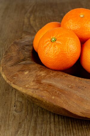 fresh mandarin orange fruits in a wooden bowl 写真素材