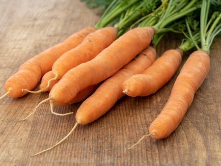 bunch bundle of carrots isolated on a wooden board with copyspace closeup