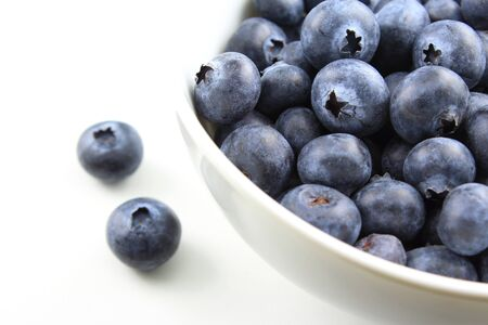 composition of fresh blueberry fruits in a small white bowl