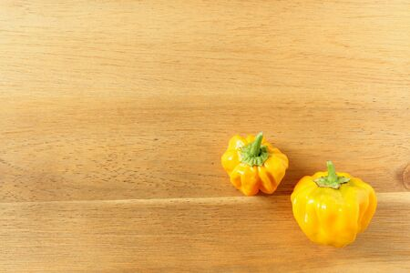 composition of fresh yellow scotch bonnet chili peppers on a wooden board with copy space