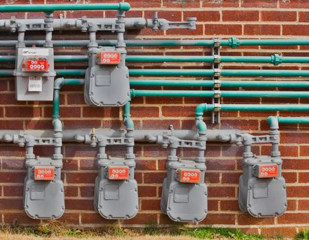 mounted: Natural gas meters mounted to a brick wall. Stock Photo