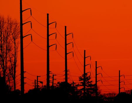 Power transmission lines silhouetted against a bright orange background