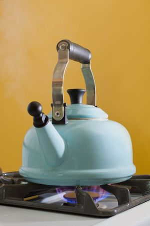 A kettle full of water boiling on a stovetop.