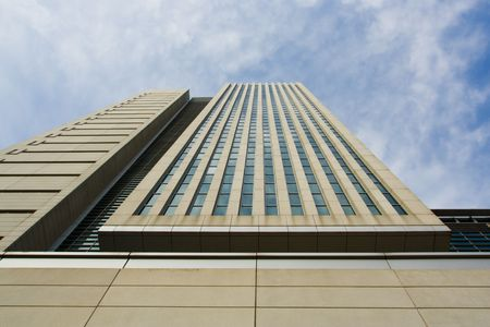 Up close photo of a tall building agast a lightly clouded blue sky Stock fotó