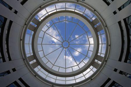 A photo looking up at a symmetrical circular skylight