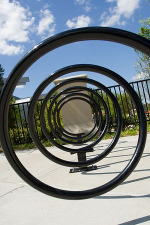 Closeup looking down a spiral bicycle rack on a sunny day Stock fotó