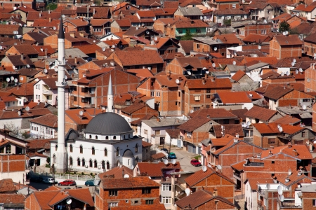 A white mosque between the red houses in the city of Prizren in Kosovo Фото со стока