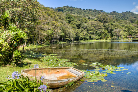 A lake with a small boat in the woods of Selva Negra near Matagalpa, Nicaragua