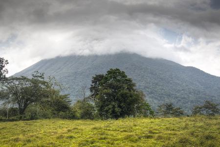 fortuna: The Arenal volcano in the national park near La Fortuna in Costa Rica semi covered in clouds