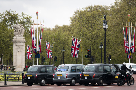 taxista: Tres taxis típicos con banderas en el fondo, en Londres, la capital del Reino Unido Editorial