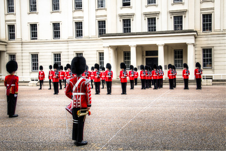 buckingham palace: The changing of the guard ceremony, with soldiers dressed authentically in red and black uniform at Buckingham Palace in London, the capital of the United Kingdom