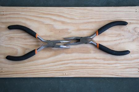 tenailles: Jeu de deux pinces sur fond de bois