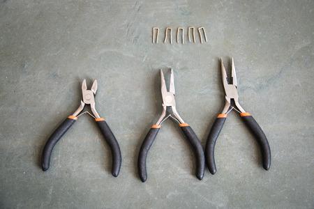 tenailles: Composition de trois petites pinces sur un fond de bois Banque d'images