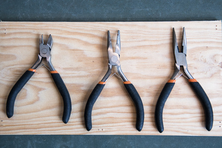 pincers: Composition of three small pincers on a wooden background Stock Photo