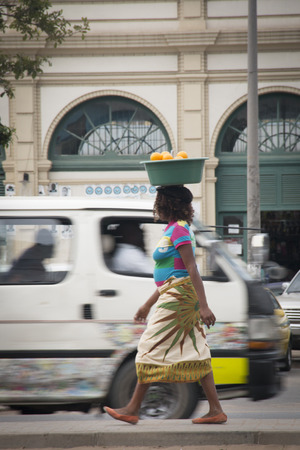 african basket: African woman with basket of oranges on her head in Maputo, Mozambique Editorial