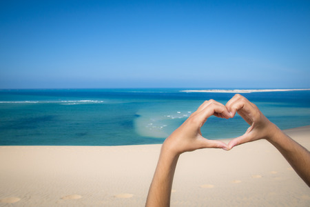 handsign: Hands making a heart sign at the beach of the Bazaruto Islands near Vilanculos in Mozambique with the Indian ocean in the background
