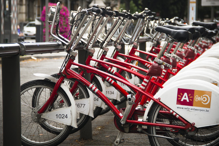 rented: A row of red city bicycles in the center of Antwerp, these bicycles can be rented Editorial