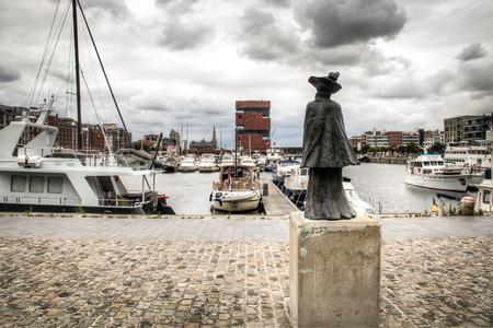 De jachthaven in de stad Antwerpen, België met een standbeeld op de voorgrond en de MAS museum in de achtergrond