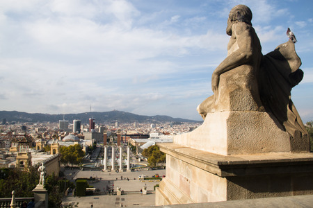 A statue with pidgins on top of Montjuic mountain with the skyline of Barcelona in the background