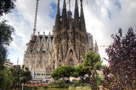 catalunia: The famous unfinished Sagrada Familia cathedral designed by Gaudi seen from the park in front of it in Barcelona in Spain Editorial
