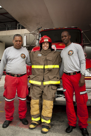 fireproof: Girl in fireproof suit posing with two firemen in front of a new fire truck Editorial