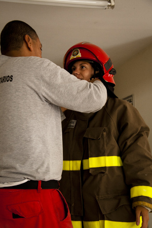 fireproof: Firaman putting a girl into a fireproof suit at the fire department of Cali, Colombia