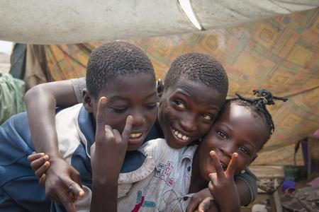 ACCRA, GHANA - Januar 2016: Drei afrikanische Kinder das Friedenszeichen in Accra, Ghana machen Editorial