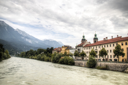 Typical Austrian houses at the embankment of the Inn river in Innsbruck, Austria with the Alps in the background Editorial