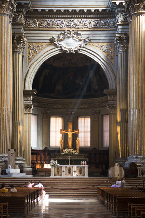 bible altar: BOLOGNA, ITALY - JULY 2016: People inside a church with a statue of Jesus on the cross in the background in Bologna in Italy Editorial