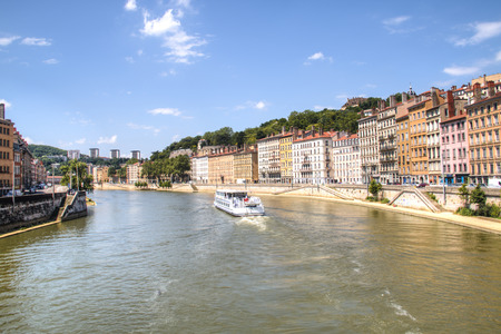 sone: LYON, FRANCE - JULY 2016: Colorful houses on the banks of the Saone river in Lyon, France with a boat passing by Editorial