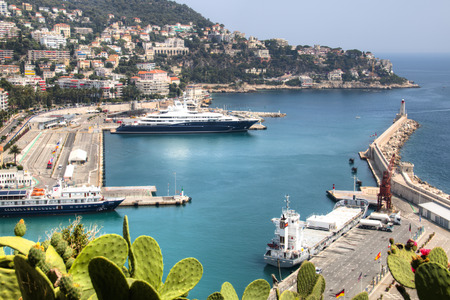 The harbor of Nice in France with some boats, seen from above from behind the cactus trees