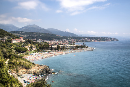 View over the coast and a village in the Liguria area in Italy with mountains in the back