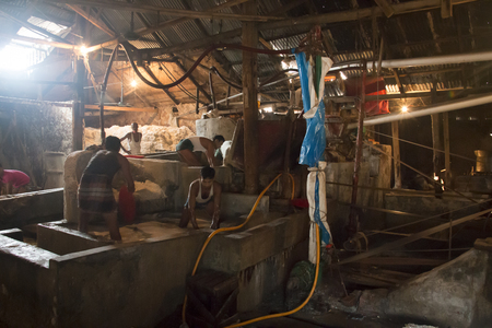 CHITTAGONG, BANGLADESH - FEBRUARY 2017: Men cleaning salt in a factory at the port of Chittagong in Bangladesh