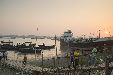 amanecer: CHITTAGONG, BANGLADESH - FEBRUARY 2017: Sunset at the port with many boats in the center of Chittagong in Bangladesh Editorial