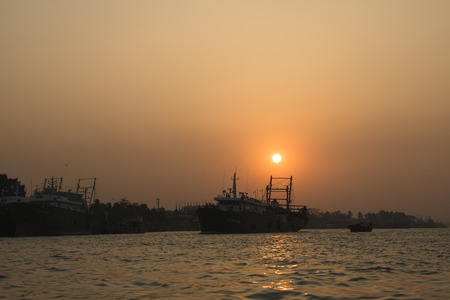 amanecer: Sunset at the port with many boats in the center of Chittagong in Bangladesh